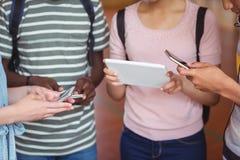 Mi section des étudiants à l'aide du téléphone portable et du comprimé numérique dans le campus Photos libres de droits