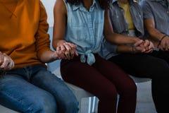 Mi section des amis tenant la main tout en se reposant sur la chaise Image libre de droits