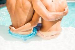 Mi section des couples embrassant tout en se reposant sur le bord de piscine Photo libre de droits