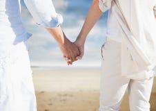 Mi section des couples tenant des mains et marchant sur la plage Images libres de droits