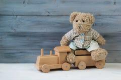 Miś siedzi na zabawkarskim drewnianym pociągu, drewniany tło Zdjęcia Stock