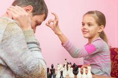 Mia figlia ha un dito sulla testa di papa, che ha perso un gioco di scacchi fotografia stock