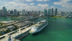 Miami aerial view buildings boats Miami river and down town. Aerial view port of Miami and down town showing cruise ships buildings convention centers and arenas stock video footage
