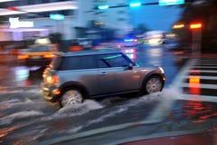 MIAMI BEACH, FL - 18-ОЕ ИЮЛЯ: Автомобили двигая дальше затопленные улицы и дороги пляжа Майами южного после проливных дождей Стоковое Изображение
