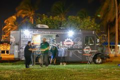 Night image of food trucks in a park. MIAMI BEACH, FL, USA - DECEMBER 26, 2017: Night image of a food truck gathering in Haulover Park kite field royalty free stock image