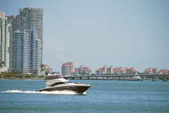 Miami Beach Lifestyle Views. View of a luxury sportfishing boat racing across the florida intercoastal while two passengers sunbathe on the forward deck in the Stock Photo
