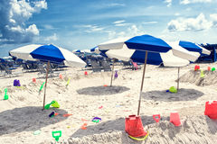 Miami Beach Scene. Colorful umbrellas lounge chairs and colorful kids sandbox toys Stock Photography