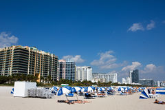 Miami Beach Sunbathers Hotels. MIAMI BEACH, FLORIDA - FEBRUARY 15, 2017: Vacationers sunbath on Miami Beach, Florida, USA, with hotels and condominiums in the Stock Image
