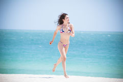 Miami Beauty. Beautiful fit model wearing a thong bikini and jogging at the gorgeous blue water beaches of florida on vacation Stock Photo