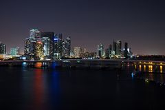 Miami city skyline panorama at dusk with urban skyscrapers and bridge over sea with reflection.  Royalty Free Stock Photos