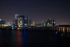 Miami city skyline panorama at dusk with urban skyscrapers and bridge over sea with reflection.  Stock Images