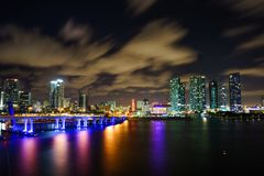 Miami city skyline panorama at dusk with urban skyscrapers and bridge over sea with reflection Royalty Free Stock Images