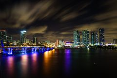Miami city skyline panorama at dusk with urban skyscrapers and bridge over sea with reflection Stock Photos