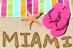 Miami, Florida beach travel background. Miami, Florida beach travel concept. MIAMI written in sand with water next to beach towel, summer sandals and starfish stock photos