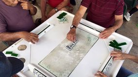 Elderly Playing Domino Game Video. Miami, Florida - February 12, 2018: Unidentified elderly individuals play the domino game in the historic Domino Park in stock video