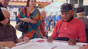 Elderly Domino Game Players Video. Miami, Florida USA - January 19, 2019: High definition video of elderly individuals playing the popular domino game at the stock footage