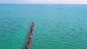 MIAMI, FLORIDA, USA - MAY 2019: Aerial drone panorama view flight over Miami beach. Breakwater pier and sea from above. MIAMI, FLORIDA, USA - MAY 2019: Aerial stock video footage