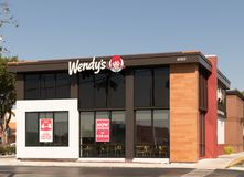 Wendy`s fast food restaurant exterior and sign. Wendy`s is the world`s third largest hamburger fast food chain with approximately Royalty Free Stock Photography