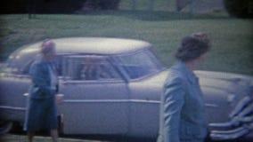 MIAMI, LA FLORIDE 1963 : Famille majestueuse arrivant dans la voiture de luxe grise à la partie dans le style banque de vidéos