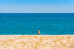 MIAMI PLATJA, ESPAÑA - 24 DE ABRIL DE 2017: La mujer está caminando a lo largo de la costa Copie el espacio para el texto fotos de archivo libres de regalías