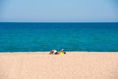 MIAMI PLATJA, SPANIEN - 24. APRIL 2017: Der Mann auf dem Strandsonnen Kopieren Sie Raum für Text Lizenzfreies Stockfoto