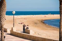 MIAMI PLATJA, SPANIEN - 24. APRIL 2017: Ein Mann macht Fotos einer Frau auf dem Damm Kopieren Sie Platz Lizenzfreies Stockbild
