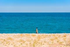 MIAMI PLATJA, SPANIEN - APRIL 24, 2017: Kvinnan promenerar kusten Kopiera utrymme för text royaltyfria foton