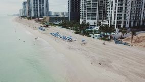 Aerial panorama the coastline of atlantic ocean with holidaymakers under umbrellas near miami hotels on sunny isles. Miami sunny isles beach with people on stock footage