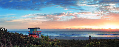 Miami sunrise. Miami South Beach sunrise panorama with lifeguard tower and coastline with colorful cloud and blue sky Stock Photos