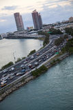 Miami traffic and skyline at dusk. Evening rush-hour traffic on Miami roadway.  Water on either side, skycrapers in background.  Image is purposely askew to give Stock Image