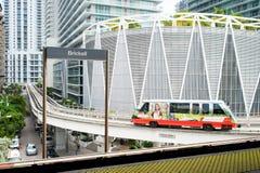 Miami, U.S.A. - 30 ottobre 2015: il treno arriva alla stazione del brickell con i grattacieli del centro su fondo urbano Metrorai Fotografie Stock Libere da Diritti