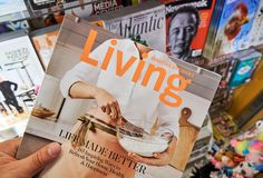 Martha Stewart Living magazine in a hand. MIAMI, USA - AUGUST 22, 2018: Martha Stewart Living magazine in a hand over a stack of magazines royalty free stock photo