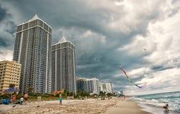 Miami, USA - January 10, 2016: sea beach and kite fly in cloudy sky. Apartment buildings on tropical coast. Architecture. Miami, USA - January 10, 2016: sea royalty free stock photography