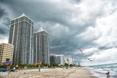 Miami, USA - January 10, 2016: sea beach and kite fly in cloudy sky. Apartment buildings on tropical coast. Architecture and real. Miami, USA - January 10, 2016 stock photo