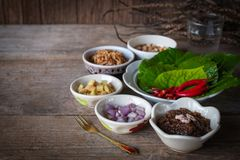 Miang kham,A royal leaf wrap appetizer Consist of Shallot, Ginger, Fried beans, Slice of lemon, Betel leaf, Chilli, Fried coconut. And chili sauce, whole placed royalty free stock photos