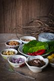 Miang kham,A royal leaf wrap appetizer Consist of Shallot, Ginger, Fried beans, Slice of lemon, Betel leaf, Chilli, Fried coconut. And chili sauce, whole placed stock image
