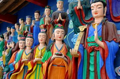 Mianyang, China: Colourful Buddhas at Temple. Detail of colourful figures in the hand-painted sculpture tableaux leading uphill to the reclining Buddha at the Stock Image