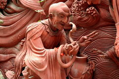 Mianyang, China: Terra Cotta Monk with Cobra. Terra Cotta sculpture of a monk holding a cobra at the historic Sheng Shui Buddhist temple, dating to the Tang and Stock Image
