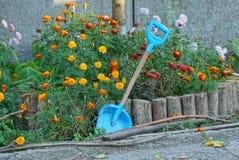 Miarki plastikowi stojaki w kwiatu łóżku z zieloną roślinnością i kwiatami zdjęcia royalty free