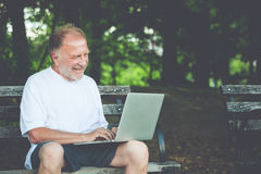 Miarowy stary facet pisać na maszynie na komputerze Obrazy Royalty Free