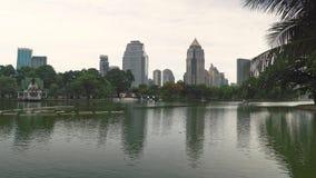 Miasta życie: dzielnica biznesu i zielony park z jeziorem dla jawnego odtwarzania Piękny pejzaż miejski, spokój zdjęcie wideo