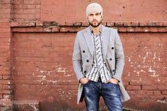 Miasta ?ycie Elegancki młody człowiek w popielatej żakieta i kapeluszu pozycji na ulicie w mieście obraz stock