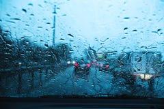 Miasto droga przez przednia szyba samochod?w t?a wody abstrakcjonistycznej kropli na szk?o deszczu i ?wiat?ach zdjęcie stock