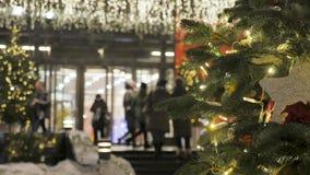 Miasto festively dekoruje W tle, ludzie wchodzić do centrum handlowe Z ostrości atmosfera świąteczna zdjęcie wideo