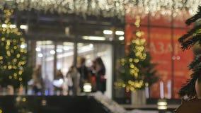 Miasto festively dekoruje W tle, ludzie wchodzić do centrum handlowe Z ostrości atmosfera świąteczna zbiory