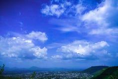 Miasto który otacza górami z pięknym niebem i chmurnieje fotografia stock