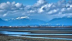 Miasto linia horyzontu, śnieżne góry i niski przypływ na granicie, Trzymać na dystans Zdjęcia Royalty Free