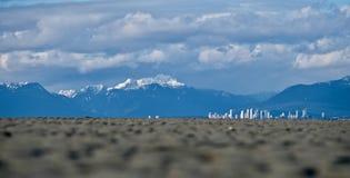 Miasto linia horyzontu, śnieżne góry i niski przypływ na granicie, Trzymać na dystans Obrazy Stock