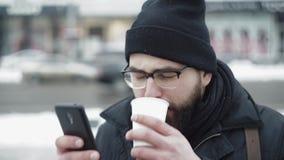 Miasto mężczyzna używa smartphone i pić herbata na zimy ulicie zbiory