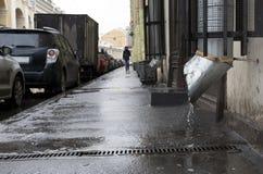 Miasto ulica, mężczyzna odprowadzenie na chodniczku deszcz, samochody parkujący Obraz Stock